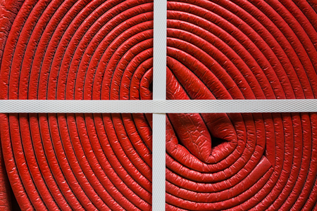 Close up red plastic pipe is as part cable coil  and is used for protective electric cables and tubes rom external actions and environment in construction and plumbing
