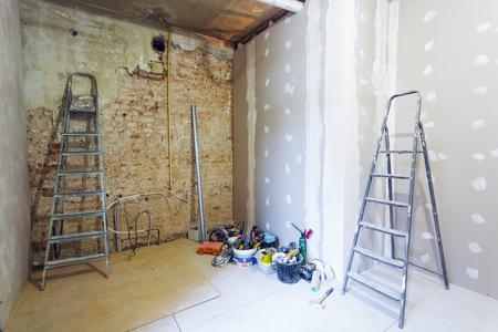 Interieur van de kamer tijdens de installatie van gipsplaat voor het maken van gipsmuren op de bakstenen muur in een appartement is in aanbouw, verbouwing, renovatie, restauratie, wederopbouw