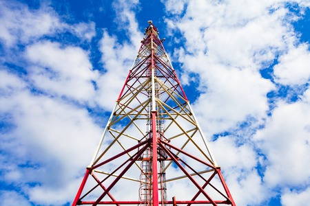 Telecommunication tower with panel antennas and radio antennas and satellite dishes for mobile communications 2G, 3G, 4G, 5G with red fence around tower against blue sky with clouds Stock Photo