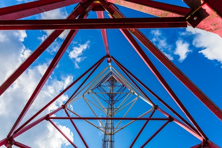 Telecommunication tower with panel antennas and radio antennas and satellite dishes for mobile communications 2G, 3G, 4G, 5G against blue sky with clouds