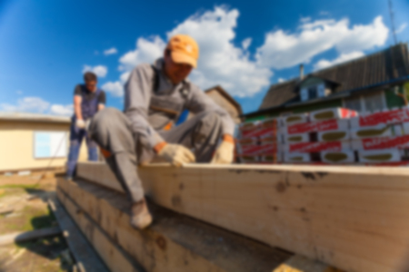 Blurred carpenters -worker -with big professional tool -electric drill- is drilling wood beam during remodeling, renovation, extension, restoration, reconstruction and construction the house