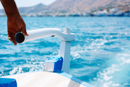 Hand of captain is controlling rudder engine on a wooden boat in the sea near island Crete. The concept of reliable and confident business management. Banco de Imagens