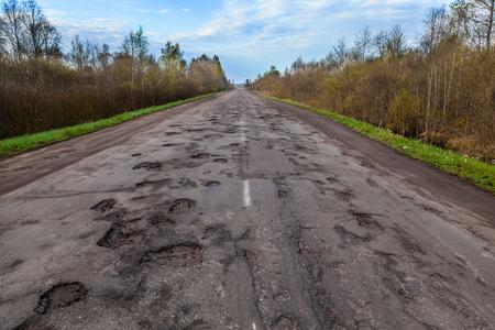 Gevaarlijke kuilen in de landelijke asfaltweg. Wegschade