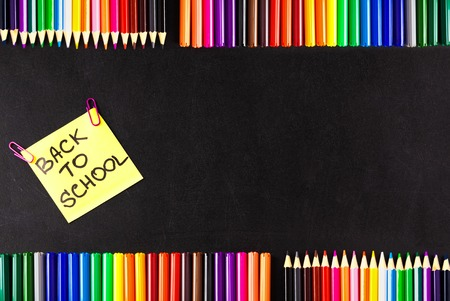 Back to school background with a lot of colorful felt-tip pens and colorful pencils, titles Back to school on the yellow piece of paper or sticker on the black scratched chalkboard.