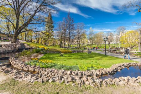 RIGA, LATVIA - MAY 06, 2017: View on  pathways with blossom trees, bushes and walking  people in The Park Bastion Hill that is located in the city center of Riga. Bastion Hill is one of the most romantic places in central Riga
