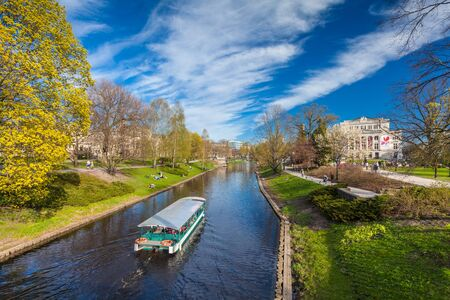 RIGA, LATVIA - MAY 06, 2017: View on the canal with pleasure craft and relaxing people onthe bank  in The Park Bastion Hill that is located in the city center of Riga.