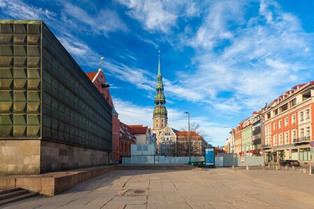 RIGA, LATVIA - MAY 06, 2017: View on the tower or cupola Rigas St.Peters Church with clock and  weathercock  and colored houses  are located in the city center of Riga