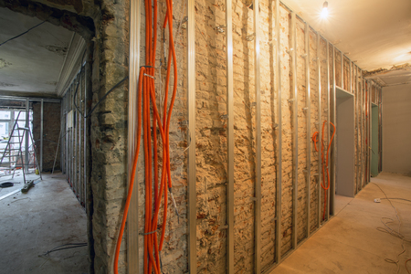 Working process of install of frames for plasterboard and corrugated pipe with electrical cables in an apartment is under construction, overhaul, remodeling, rebuilding, home improvements, reconstruction  and renovation. Stockfoto