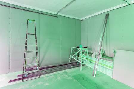 Green interior of apartment  during construction, remodeling, renovation, extension, restoration and reconstruction - ladder and construction materials in the room