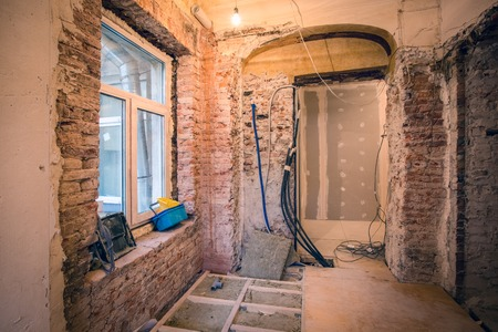 Interior of small room with window and bricks walls in an apartment that  is under construction, remodeling, renovation, extension, overhaul  and reconstruction.