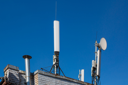 Panel antennas of GSM DCS UMTS LTE bands, optical fibers, power cables and outdoor remote radio units are as part of communication equipment of basic telecommunication station are installed on the roof and blue sky as background.