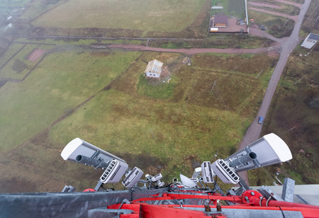 Red telecommunication tower or mast with microwave, radio panel antennas, outdoor remote radio units, power cables, coaxial cables, optic fibers are on the top in foggy day and ground with buildings, roads and houses are as background. View from top to down of tower.