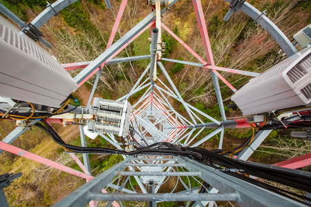 Red telecommunication tower or mast with microwave, radio panel antennas, outdoor remote radio units, power cables, coaxial cables, optic fibers are on the top mast that located in forest . View from top to down of tower.