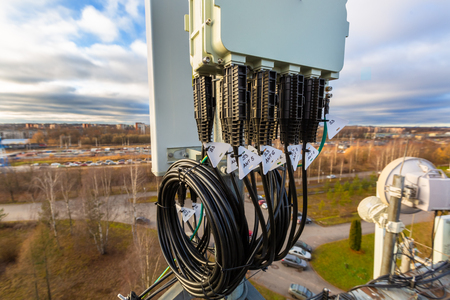 Panel antenna of GSM DCS UMTS LTE bands, GPS antenna and remote radio unit are as part of communication equipment of basic station are installed on the tubular mast and sky and city are as background.