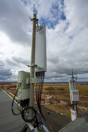 Panel antenna of GSM DCS UMTS LTE bands, GPS antenna and outdoor remote radio unit are as part of communication equipment of basic station are installed on the tubular mast on the roof Stock Photo - 116174494