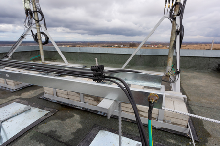 Panel antenna of GSM DCS UMTS LTE bands and radio unit are installed on the tubular mast are as part of communication equipment of basic station are installed on the roof and cable tray with power and optic cables
