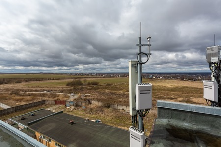 Panel antenna of GSM DCS UMTS LTE bands, GPS antenna and outdoor remote radio unit are as part of communication equipment of basic station are installed on the tubular mast on the roof