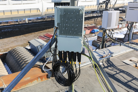 Panel antenna of GSM DCS UMTS LTE bands and outdoor remote radio unit are as part of communication equipment of basic station are installed on the tubular mast on the roof