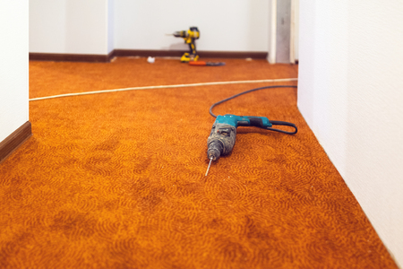Battery screwdriver and electrical drill - are construction hand  tools  for home improvement, construction, renovation, for fixing skirtboard and carpet  on the floor.  Construction, remodeling, reno 写真素材