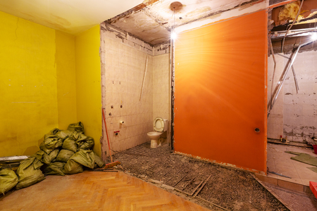 Toilet room or restroom with old toilet bowl, bags with construction trash are in apartment that is under construction, remodeling, renovation, overhaul, extension, restoration and reconstruction. Concept of total home improvement. Banque d'images