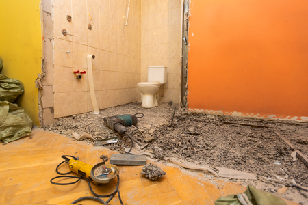 Toilet room or restroom with old toilet bowl and construction tools - perforator and angle grinder are in apartment that is under construction, remodeling, renovation, overhaul, extension, restoration and reconstruction. Concept of total home improvement.