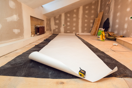 Working process of wallpapering  on the drywall in small room apartment is under construction, remodeling, renovation, extension, restoration and reconstruction. Paperhangings is measured by tape-measure on the floor and cut. Concept of home improvement. 写真素材