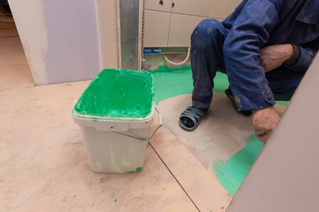 Construction level  on the foreground and  worker is working with palette-knife  for flattening  of spackling compound in apartment is inder construction, remodeling, renovation, overhaul, extension,