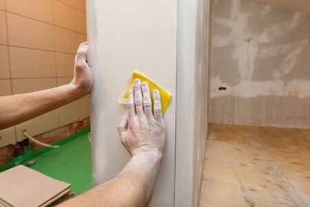 Worker hands is troweling by sandpaper the room wall in an apartment is inder construction, remodeling, renovation, overhaul, extension, restoration and reconstruction. Concept of home improvement or