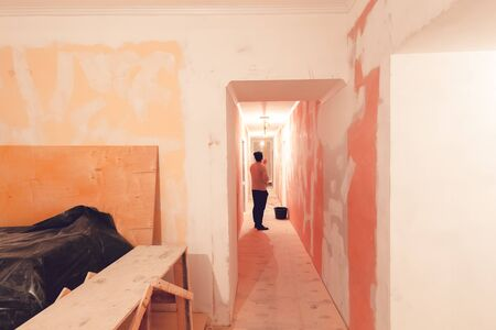 Worker is painting the ceiling by paint roller in corridor  an apartment is inder construction, remodeling, renovation, overhaul, extension, restoration and reconstruction. Concept of home improvement 写真素材