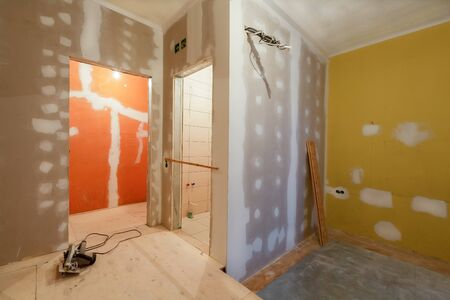 Working process of installing   plasterboard or drywall  for making gypsum walls  in apartment is under construction, remodeling, renovation, extension, restoration and reconstruction.  Concept of home improvement or renovate.