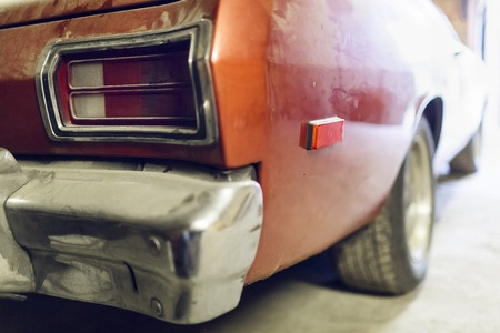 Restoration of classic red car. Close up view front side classic car and  bumper of  broken dusty car during road accident and has been reconstructed in garage. Restoration of classic car.
