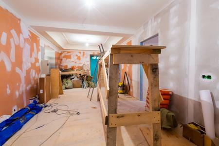 El proceso de trabajo de renovación de la habitación de la plataforma de madera, cables eléctricos y materiales de construcción en el apartamento está en construcción, remodelación, renovación, ampliación, restauración y reconstrucción. Foto de archivo
