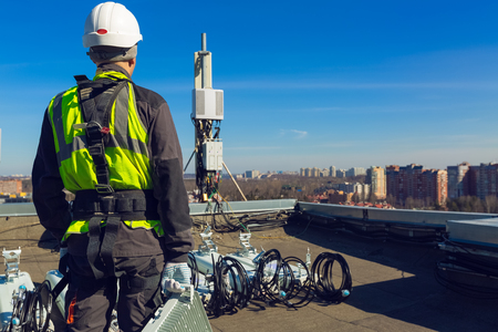 Professional industrial climber in helmet and uniform with telecomunication equipment in his hand and antennas of GSM DCS UMTS LTE bands, outdoor radio units on the roof. Working process of upgrading telecommunication equipment.