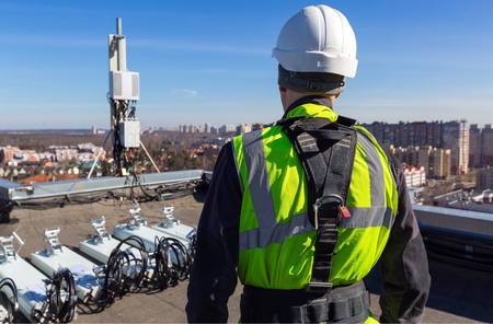 Professional industrial climber in helmet and uniform  and  antennas of GSM  DCS UMTS LTE bands, outdoor radio units  on the roof. Working process of upgrading telecommunication equipment.