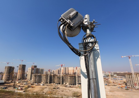 Panel antenna of GSM DCS UMTS LTE bands and radio unit are as part of communication equipment of basic station are installed on the roof and sky and city are as background