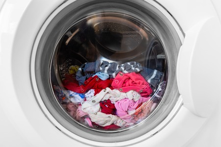 Closed round washing machine door with rotating garments inside. Focus in the center of dirty laundry and washing machine on the frame.