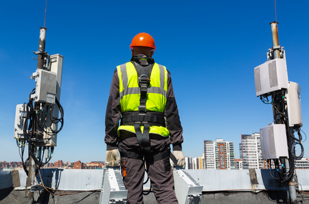 Professional industrial climber   in helmet and uniform holds telecomunication equipment in his hand and  antennas of GSM  DCS UMTS LTE bands, outdoor radio units, optic fibers, power cables are installed on the roof. Working process of upgrading telecommunication equipment