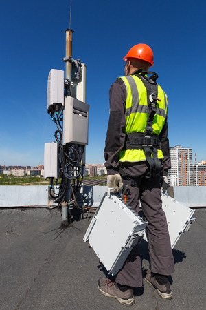 Telecommunication engineer  in helmet and uniform holds telecomunication equipment in his hand and  antennas of GSM  DCS UMTS LTE bands, outdoor radio units, optic fibers, power cables are installed on the roof. Working process of upgrading telecommunication equipment