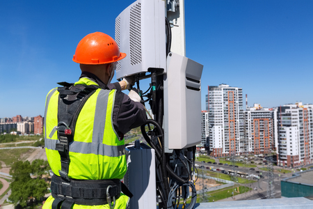 Telecommunication engineer  in helmet and uniform installs telecomunication equipment in his hand and  antennas of GSM  DCS UMTS LTE bands, outdoor radio units, optic fibers, power cables are installed on the roof. Working process of upgrading telecommunication equipment Фото со стока