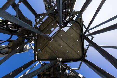 Wieża telekomunikacyjna lub maszt z mikrofalą, anteny panelowe radiowe, zewnętrzne radiostacje zdalne, kable zasilające, kable koncentryczne, światłowody znajdują się na szczycie masztu zlokalizowanego w mieście
