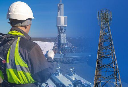 Kolaż inżyniera telekomunikacji w hełmie i mundurze z dokumentacją oraz wieża z antenami pasma GSM DCS UMTS LTE, radiostacje zewnętrzne na dachu. Proces roboczy modernizacji sprzętu telekomunikacyjnego.