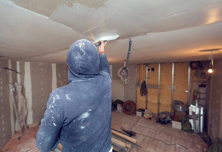 Worker is working with palette-knife for flattening  the ceiling from wooden platform in room of  apartment is inder construction, remodeling, renovation, overhaul, extension, restoration and reconstruction. Concept of home improvement. Banco de Imagens