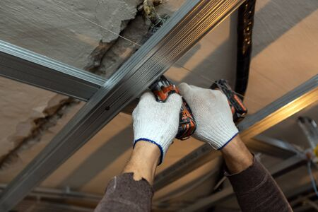 Worker with protective gloves is drilling by perforator the ceiling for installing metall frames  in apartment that is under construction, remodeling, renovation, overhaul, extension, restoration and reconstruction. Concept of total home improvement. Banco de Imagens