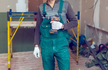Worker with protective gloves is holdind a perforator with some drywall screws  in apartment that is under construction, remodeling, renovation, overhaul, extension, restoration and reconstruction. Concept of total home improvement or renovate.