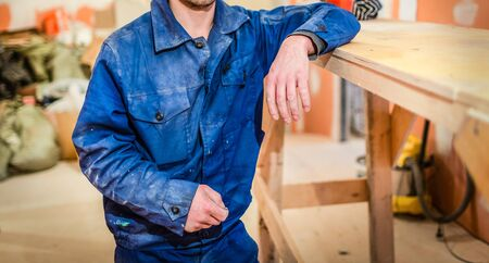 Worker in dirty blue uniform is staying in apartment that is under construction, remodeling, renovation, overhaul, extension, restoration and reconstruction. Concept of total home improvement or renov