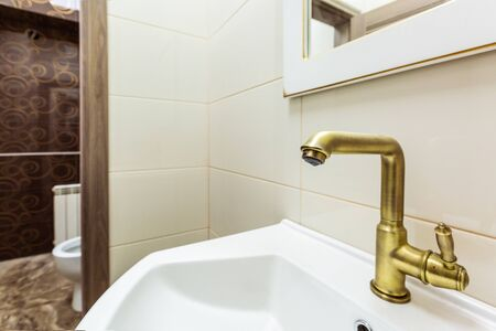 Modern cuprum faucet with falling water drop and sink in toilet room