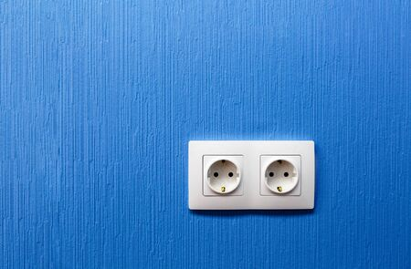 Double electrical socket and outlet on blue painted wall in the room in apartment is after construction, remodeling, renovation, extension, restoration and reconstruction. Space for your text.