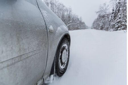 View focused on the car tire during in motion on snowy rural road during snowfall.