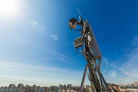 Telecommunication data equipment with microwave radio antennas, outdoor remote radio units, power cables, coaxial cables, optic fibers. Outside part of telecommunication basic station over city Stockfoto