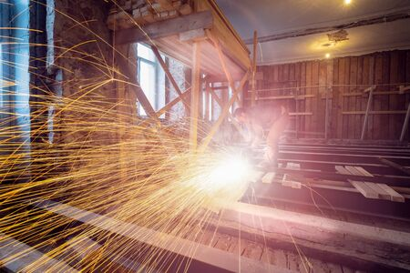 Worker is using angle grinder and fountain of sparks in apartment that is under construction, remodeling, renovation, extension, restoration and reconstruction. Concept of total home improvement.